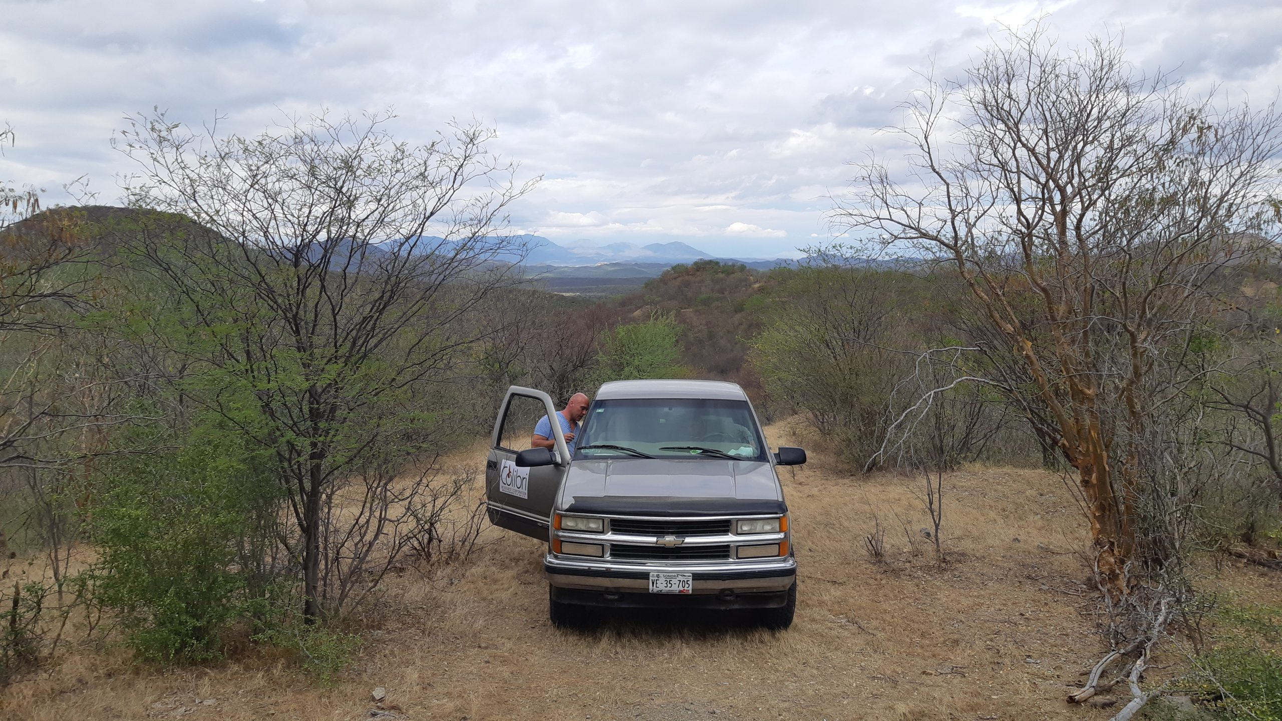 Truck parked on access trail, looking West to town of Suaqui Grande at Pilar